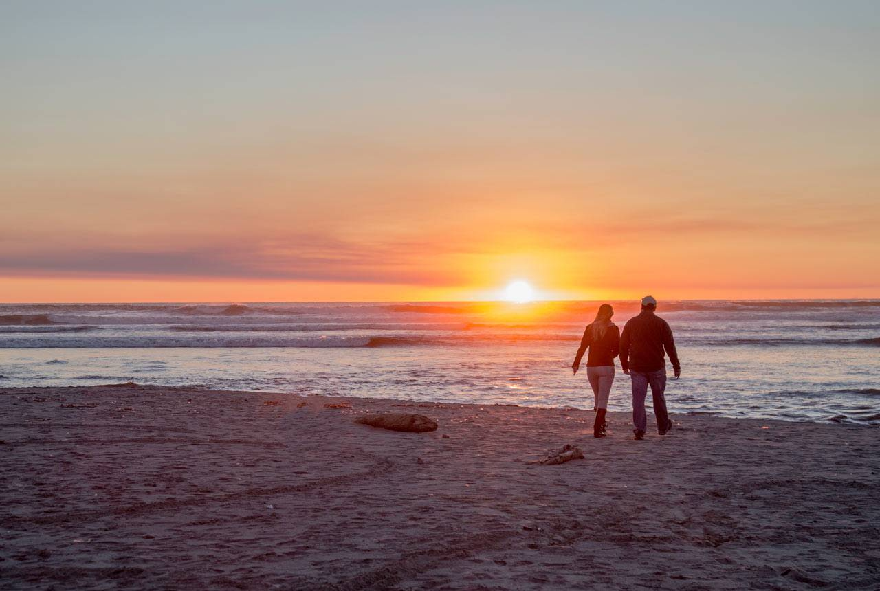 A couple walks along Kalaloch Beach at sunset